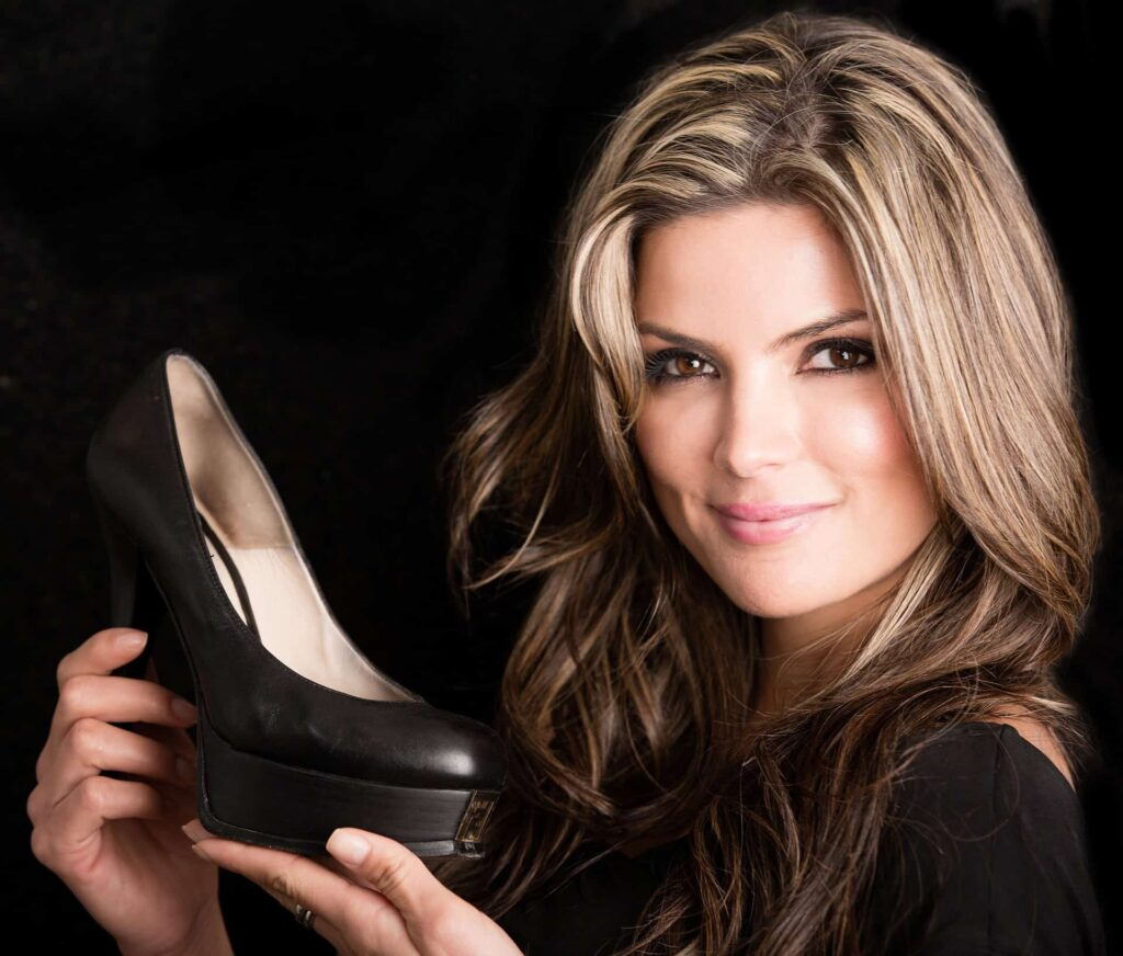 Fashion woman holding shoes - isolated over black background